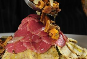 South Tyrolean Style canederli slices with beef carpaccio and marinated chanterelle mushrooms