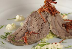 Boiled beef cheek on marinated cabbage salad with fried Speck Alto Adige