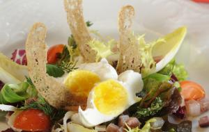 Poached free range egg on herbed salad and ox tongue salad