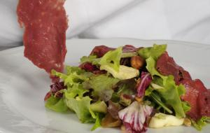 Venison carpaccio with dried fruit on crunchy salad